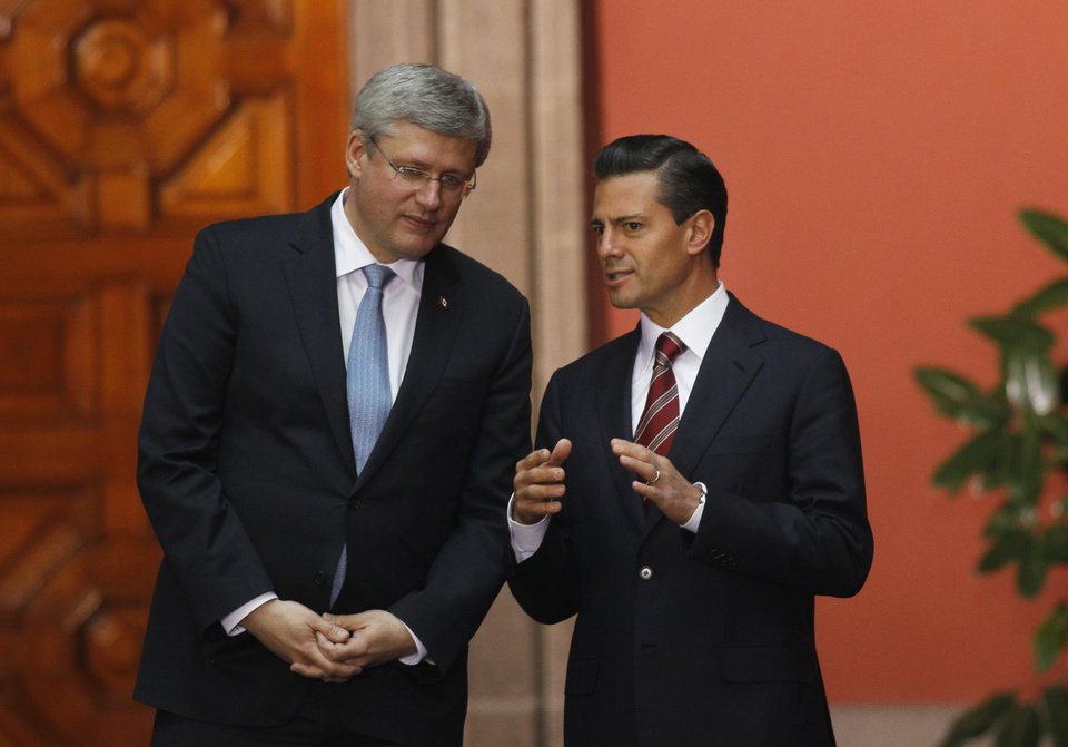Photo - Mexico's President Enrique Pena Nieto, right, with Canada's Prime Minister Stephen Harper pose for photographers after giving a joint news conference at the National Palace in Mexico City, Tuesday, Feb. 18, 2014. The two met in a warm-up of sorts for Wednesday, when the they will join U.S. President Barack Obama at their North American leaders' one-day summit. (AP Photo/Marco Ugarte)