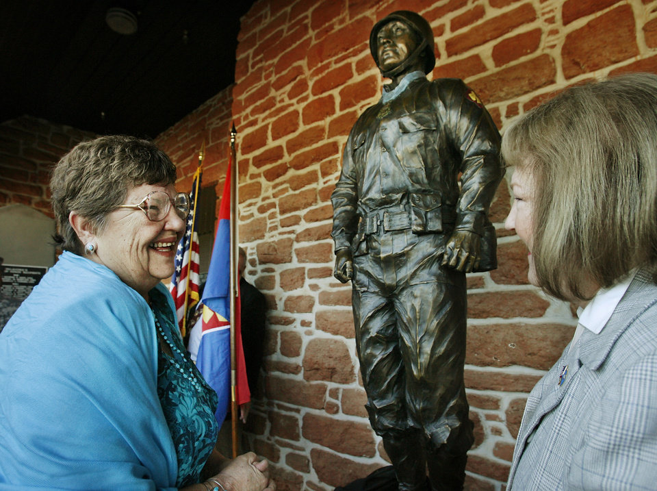 Photo - UNVEILING / ART: Yolanda Childers, left, of Tulsa,  expresses her delight with the newly dedicated statue of her father, Ernest Childers, with sculptor Sandra Van Zandt after the artwork was unveiled during a ceremony at the 45th Infantry Division Museum in Oklahoma City Friday morning, Sept. 25, 2009. Childers, a member of the 45th during World War II,  is a Medal of Honor recipient.   Photo by Jim Beckel, The Oklahoman ORG XMIT: KOD