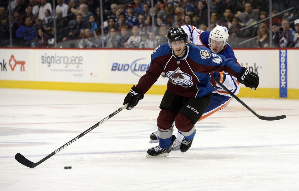 Colorado Avalanche's Michael Sgarbossa, left, advances the puck past Edmonton Oilers' Lennart Petrell in the third period of an NHL hockey game in Denver, Saturday, Feb. 13, 2013. The Avalanche won 3-1. (AP Photo/The Denver Post, Andy Cross)  MAGAZINES OUT; TV OUT; INTERNET OUT; NO SALES