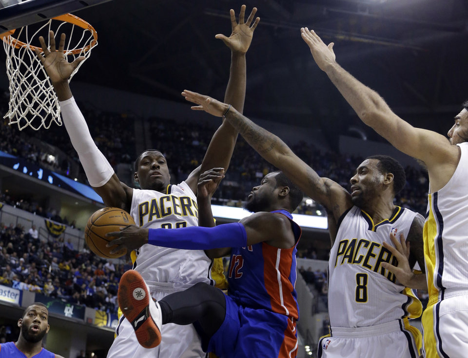 Photo - Detroit Pistons guard Will Bynum, left center, makes a pass between Indiana Pacers' Ian Mahinmi, left, Rasual Butler, right center, and Luis Scola in the first half of an NBA basketball game in Indianapolis, Monday, Dec. 16, 2013.  (AP Photo/Michael Conroy)