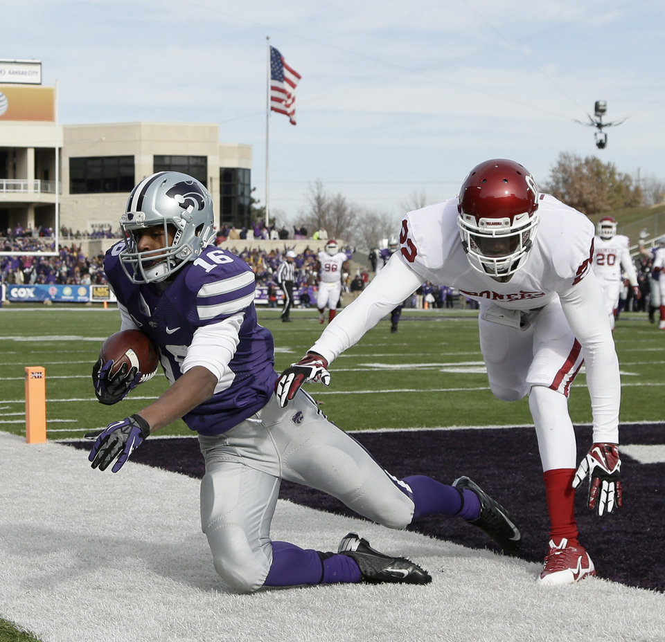 Kansas State wide receiver Tyler Lockett (16) falls out of bounds with Oklahoma defensive back Cortez Johnson (22) after catching a pass to score a touchdown during the first half of an NCAA college football game Saturday, Nov. 23, 2013 in Manhattan, Kan. (AP Photo/Charlie Riedel)