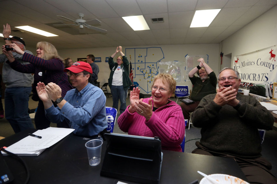 Photo -   John Dockendorff, from left, Roxy and John Riessen, along with others react to projections that President Obama won the election, during an election night watch party, Tuesday Nov. 6, 2012 at the Des Moines County Democratic Headquarters in Burlington, Iowa. (AP Photo/The Hawk Eye, John Lovretta)