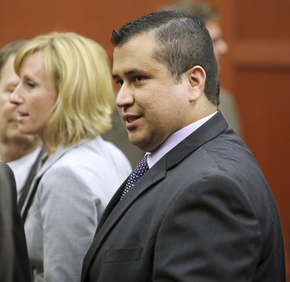 Photo - George Zimmerman leaves court with his family after Zimmerman's not guilty verdict was read in Seminole Circuit Court in Sanford, Fla. on Saturday, July 13, 2013. Jurors found Zimmerman not guilty of second-degree murder in the fatal shooting of 17-year-old Trayvon Martin in Sanford, Fla. (AP Photo/Joe Burbank, Pool) ORG XMIT: FLJR410