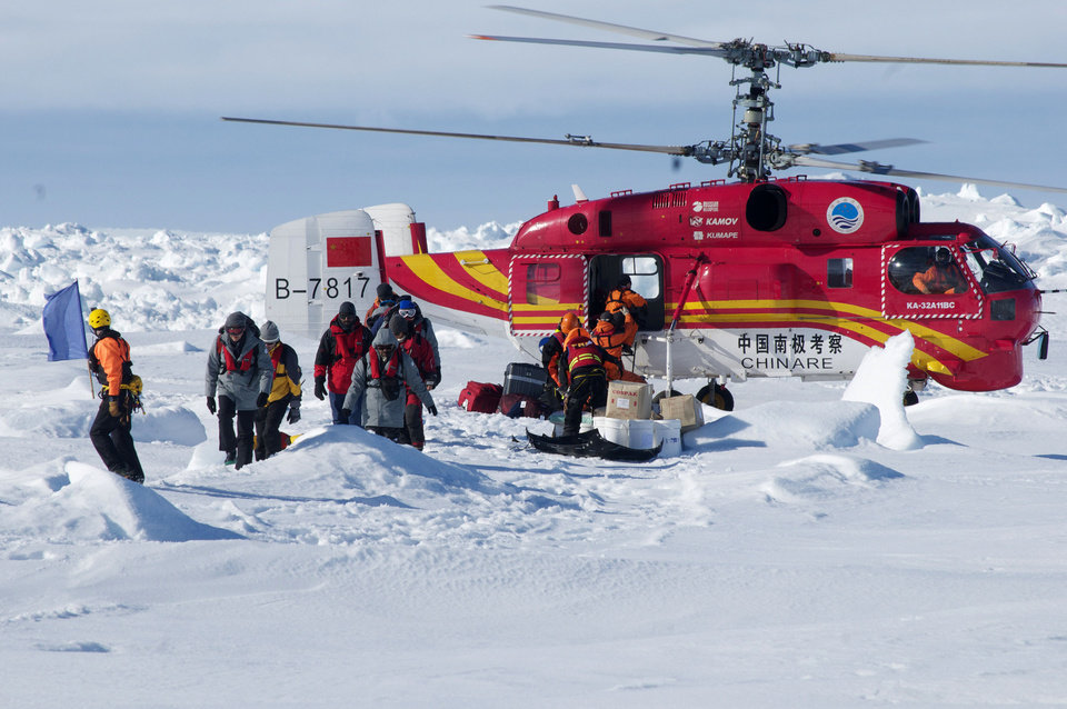 Photo - In this image provided by Australasian Antarctic Expedition, A Chinese helicopter arrives to rescue some of the 52 passengers trapped for more than a week on the icebound Russian research ship MV Akademik Shokalskiyin , Thursday, Jan. 2, 2014.  The helicopter rescued all 52 passengers from the research ship that has been trapped in Antarctic ice, 1,500 nautical miles south of Hobart, Australia, since Christmas Eve after weather conditions finally cleared enough for the operation Thursday. (AP Photo/Australasian Antarctic Expedition, Jessica Fitzpatrick) EDITORIAL USE ONLY, ONE TIME USE ONLY, NO ARCHIVES; NO SALES