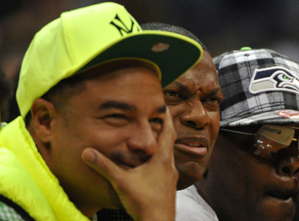Photo - Actor Chris Tucker, center, makes a face as he watches the Atlanta Hawks play the Toronto Raptors in the first half of their NBA basketball game Tuesday, March 18, 2014, in Atlanta. (AP Photo/David Tulis)