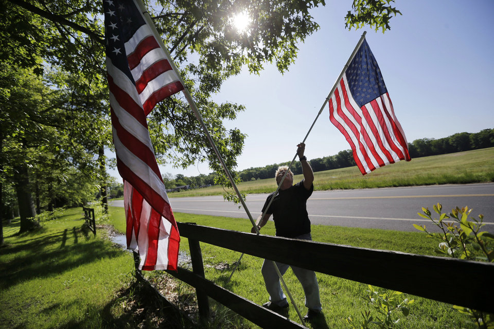 Photo - Bob Petersen places flags along a fence for the Memorial Day weekend, at his home in the Cream Ridge section of Upper Freehold, N.J., Sunday, May 25, 2014. (Mel Evans)