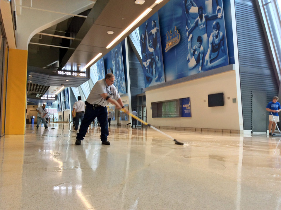 Photo - A worker clears water from the lobby floor of Pauley Pavilion, home of UCLA basketball, after a 30-inch water main burst on nearby Sunset Boulevard Tuesday, July 29, 2014, in Loss Angeles. Water also reached the playing floor of the basketball arena. (AP Photo/Matt Hamilton)