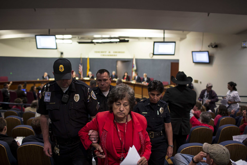 Photo - Activist Nora Tachias-Anaya is escorted from a city council meeting in Albuquerque, N.M., Thursday, May 8, 2014. At least seven people were removed from the chambers and given a criminal trespass notice saying not to return to council chambers for 90 days. The Albuquerque City Council gathered Thursday under new rules and heightened security designed to avoid an angry confrontation like the one that broke out earlier in the week amid community outrage over a spate of deadly police shootings. (AP Photo/Juan Antonio Labreche)