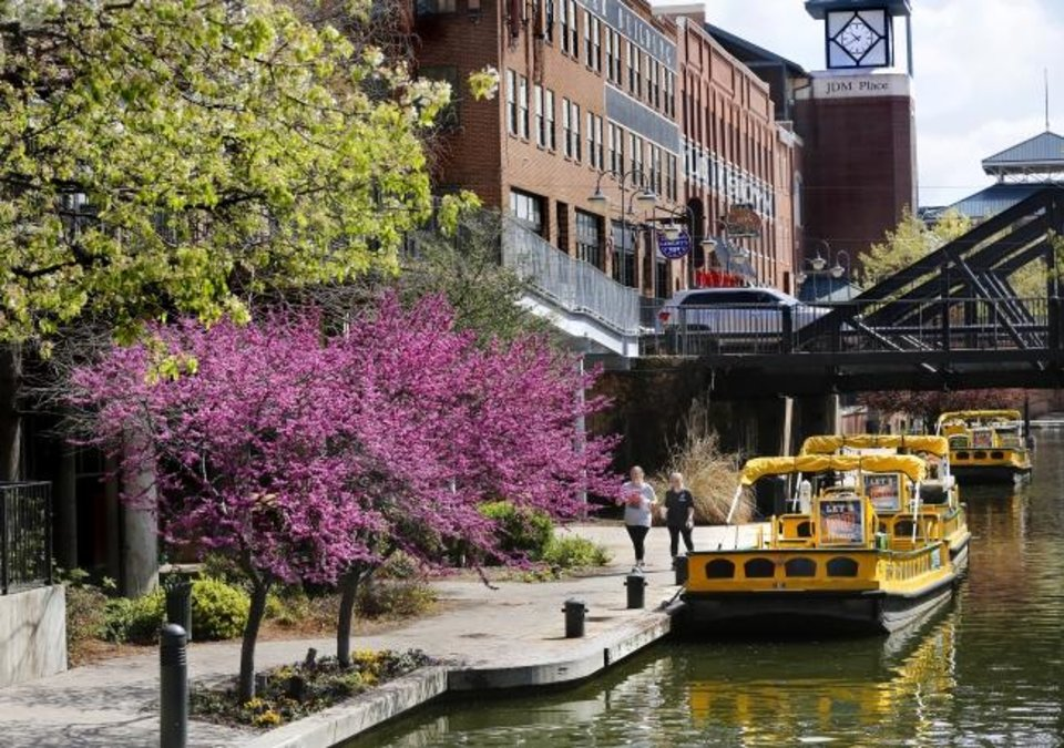 Photo -  Women enjoy a walk along the Bricktown Canal on a pleasant spring afternoon recently in downtown Oklahoma City. [Jim Beckel/The Oklahoman]