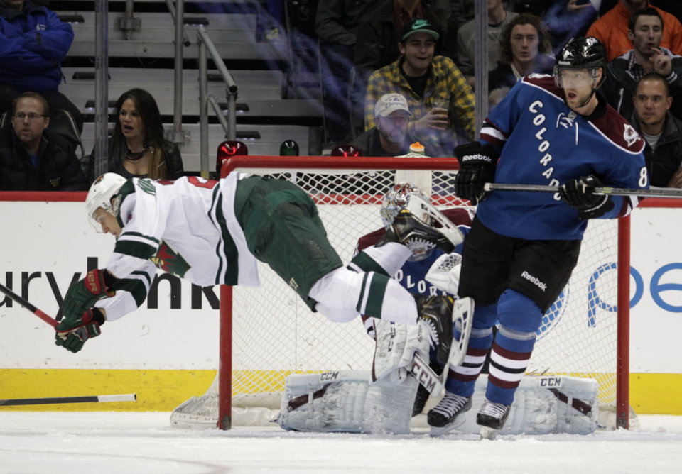 Photo - Minnesota Wild right wing Nino Niederreiter, left, dives across the crease against Colorado Avalanche goalie Semyon Varlamov, center, and Avalanche defenseman Jan Hejda during the first period of an NHL hockey game in Denver on Saturday, Dec. 14, 2013. (AP Photo/Joe Mahoney)