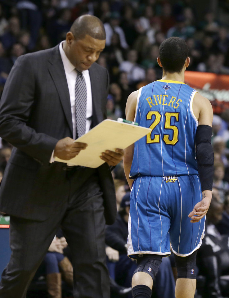 Photo - Boston Celtics head coach Doc Rivers, left, looks at his clipboard as his son, New Orleans Hornets shooting guard Austin Rivers (25), walks toward his bench late in the fourth quarter of an NBA basketball game in Boston, Wednesday, Jan. 16, 2013. The Hornets won 90-78. (AP Photo/Elise Amendola)