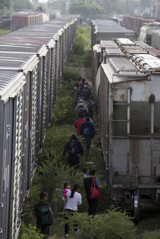 Photo - In this July 12, 2014, photo, migrants walk in between parked trains after getting off one, during their journey toward the U.S.-Mexico border in Ixtepec, southern Mexico. Tens of thousands of unaccompanied minors, the vast majority from Guatemala, El Salvador and Honduras, have been apprehended at the U.S. border from last October to June, according to the Border Patrol. That's more than double the same period last year. (AP Photo/Eduardo Verdugo)