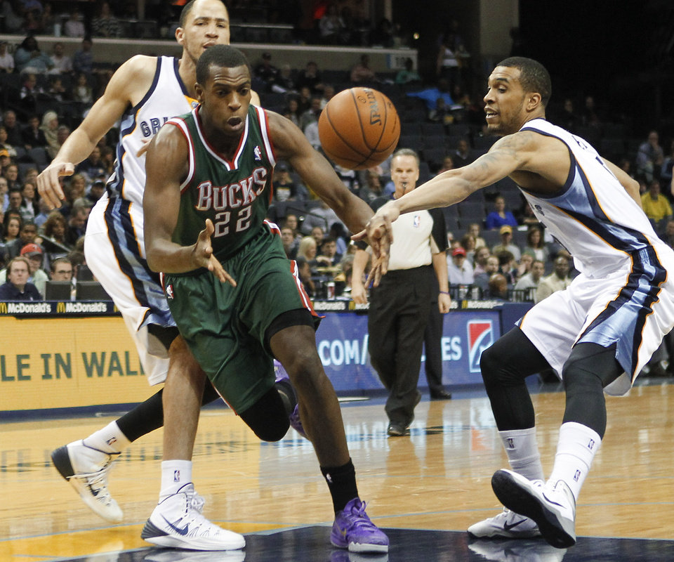 Photo - Memphis Grizzlies forward Courtney Lee, right, and forward Tayshaun Prince, back left, strip the ball from Milwaukee Bucks forward Khris Middleton (22) in the first half of an NBA basketball game on Saturday, Feb. 1, 2014, in Memphis, Tenn. (AP Photo/Lance Murphey)