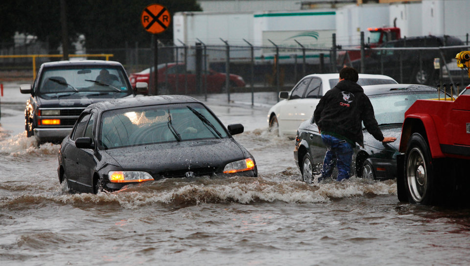 A wrecker driver hooks cables to a stranded car intersection of Western at NW 4. Torrential rain caused flooding in Oklahoma City, Monday, June 14, 2010. by Jim Beckel, The Oklahoman
