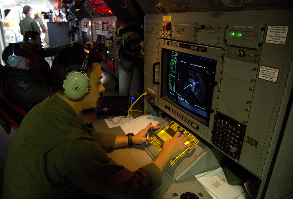 Photo - FILE - In this Thursday, March 27, 2014, file photo, Sgt. Matthew Falanga, an airborne electronics analyst, observes a radar image aboard a Royal Australian Air Force AP-3C Orion aircraft during a search operation of the missing Malaysian Airlines Flight 370 over the southern Indian Ocean. The disappearance of the airplane has presented two tales of modern technology. The public has been surprised to learn of the limitations of tracking and communications devices, which contributed to the plane vanishing for more than two weeks. But the advanced capabilities of some technologies, particularly satellites, have provided hope that the mystery won't go unsolved. (AP Photo/Michael Martina, Pool, File)
