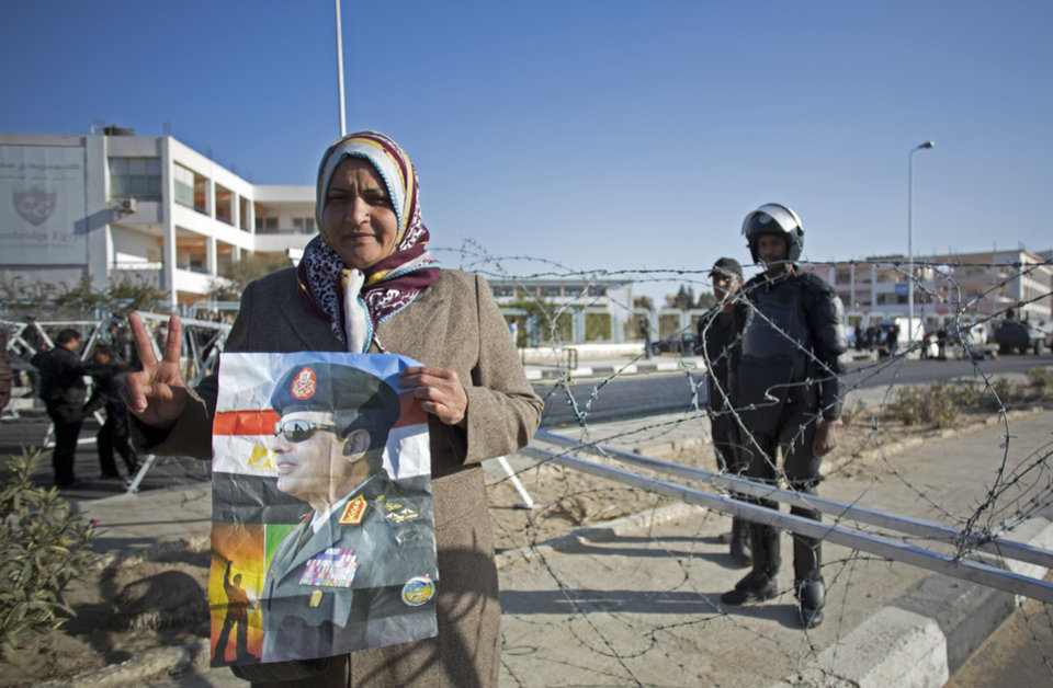 Photo - An Egyptian woman flashes the victory sign and holds a picture of Egypt's Defense Minister Field Marshal Abdel-Fattah el-Sissi, while  police guard outside the courthouse during the trial of ousted Egyptian President, Mohammed Morsi, in Cairo, Egypt, Tuesday, Jan. 28, 2014. Morsi has arrived in Cairo by helicopter from Borg al-Arab prison near Alexandria for the start of his trial Tuesday over charges he and some 130 others face for prison breaks during the country's 2011 revolution, the state news agency reported. (AP Photo/Khalil Hamra)