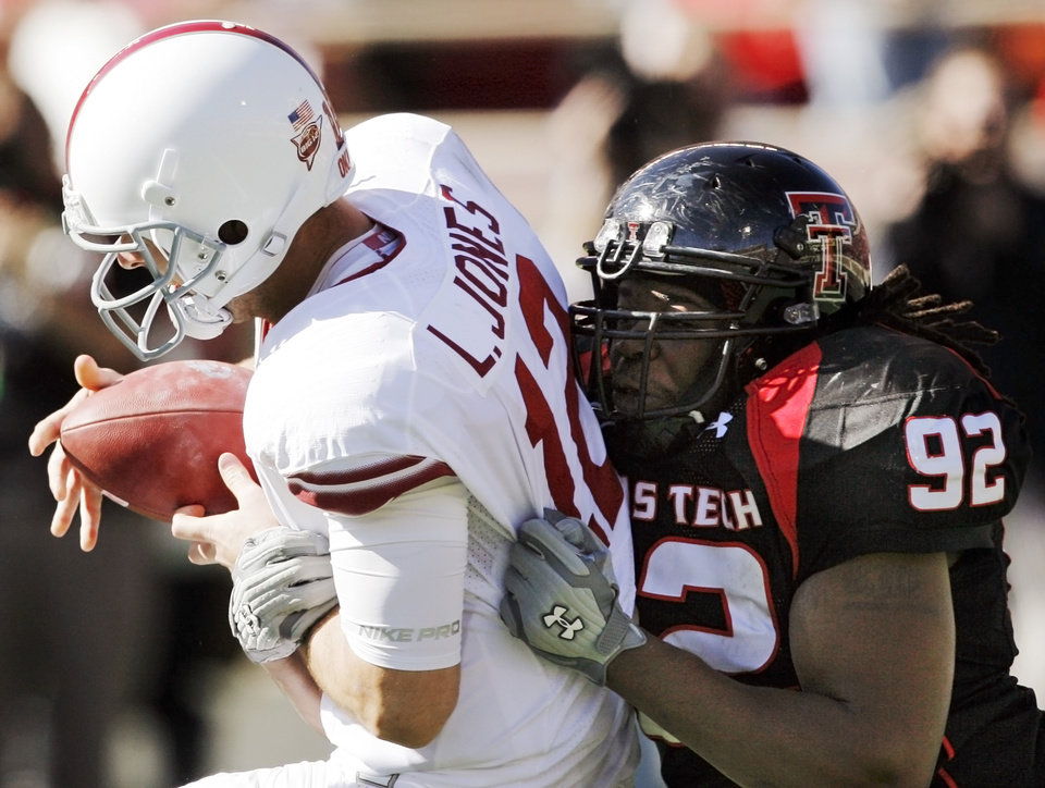 Texas Tech's Brandon Sharpe (92) sacks OU quarterback Landry Jones (12) during the college football game between the University of Oklahoma Sooners (OU) and the Texas Tech University Red Raiders (TTU) at Jones AT&T Stadium in Lubbock, Texas, Saturday, Nov. 21, 2009. Photo by Nate Billings, The Oklahoman