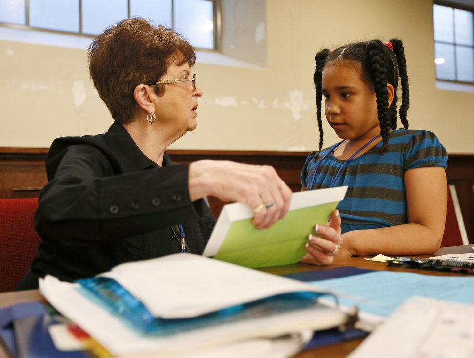 Photo - Sally Liles, a volunteer from United Methodist Church of the Servant, works with Fantasia Arredondo, 6, during a Whiz Kids session at Wesley United Methodist, 1401 NW 25.   NATE BILLINGS - NATE BILLINGS