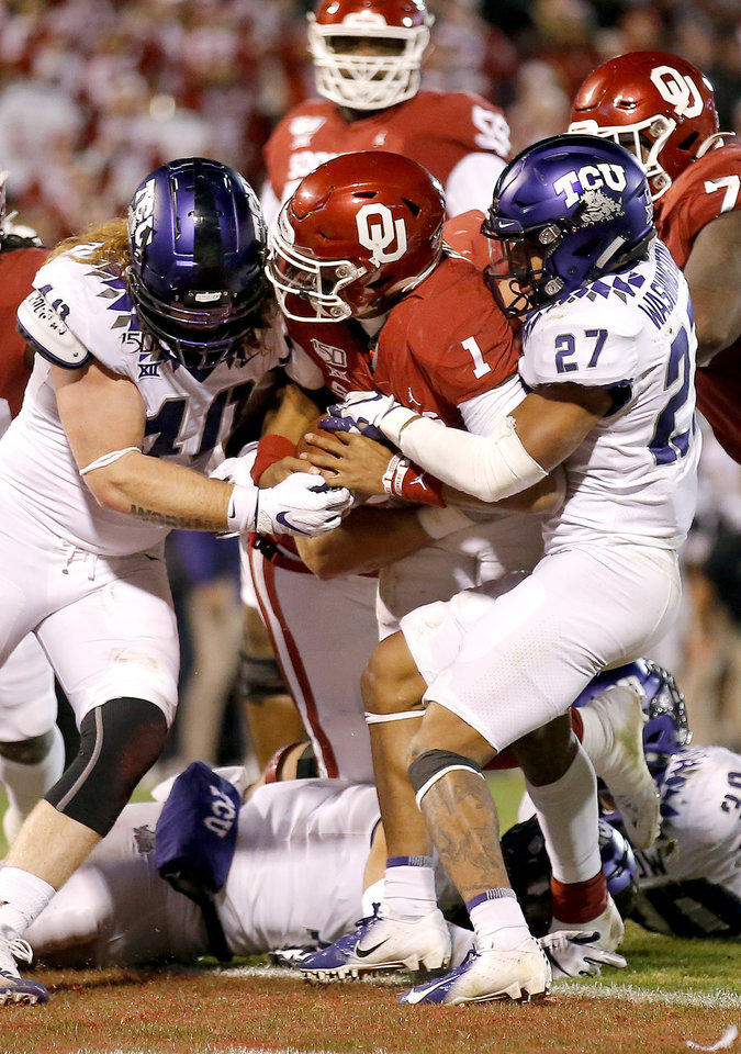 Photo - Oklahoma's Jalen Hurts (1) scores a touchdown in the third quarter as TCU's Parker Workman (40) and Ar'Darius Washington (27) defend during an NCAA football game between the University of Oklahoma Sooners (OU) and the TCU Horned Frogs at Gaylord Family-Oklahoma Memorial Stadium in Norman, Okla., Saturday, Nov. 23, 2019. OU won 28-24. [Sarah Phipps/The Oklahoman]