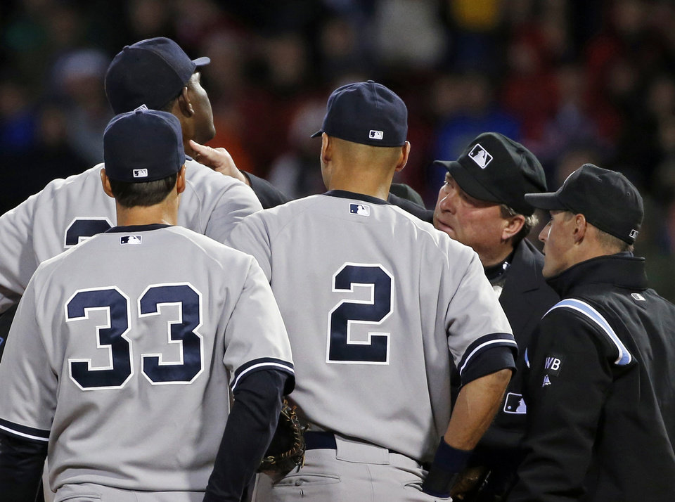 Photo - Home plate umpire Gerry Davis touches the neck of New York Yankees starting pitcher Michael Pineda in the second inning of the Yankees' baseball game against the Boston Red Sox at Fenway Park in Boston, Wednesday, April 23, 2014. Pineda was ejected after umpires found with a foreign substance on his neck. (AP Photo/Elise Amendola)