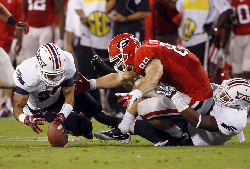 Photo -   Georgia tight end Arthur Lynch (88) fumbles as he is tackled by Florida Atlantic defensive back D'Joun Smith, right, during the first half of an NCAA college football game Saturday, Sept. 15, 2012, in Athens, Ga. Florida Atlantic defensive back Anthony Hamilton, left, recovered the fumble. (AP Photo/John Bazemore)