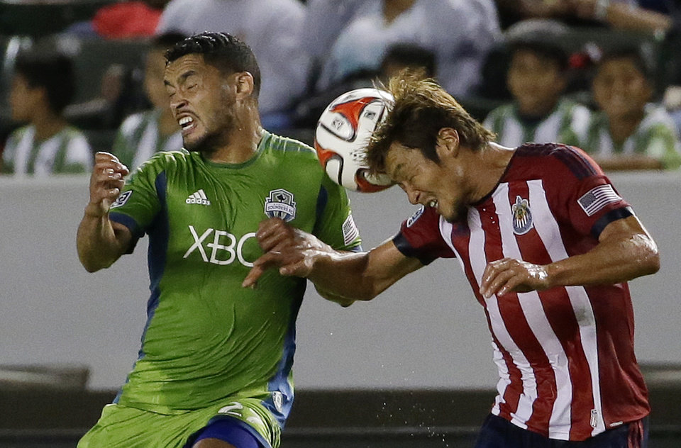 Photo - Chivas USA's Akira Kaji, right, heads the ball away from Seattle Sounders' Lamar Neagle during the first period of an MLS soccer match Wednesday, Sept. 3, 2014, in Carson, Calif. (AP Photo/Chris Carlson)