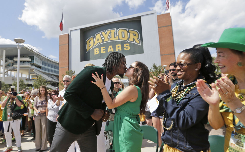 Photo - Washington Redskins quarterback Robert Griffin III, left, kisses his wife Rebecca before the dedication of a statute outside the new McLane Stadium before an NCAA college football game between SMU and Baylor Sunday, Aug. 31, 2014, in Waco, Texas. Griffin won the Heisman Trophy when he played at Baylor. (AP Photo/LM Otero)