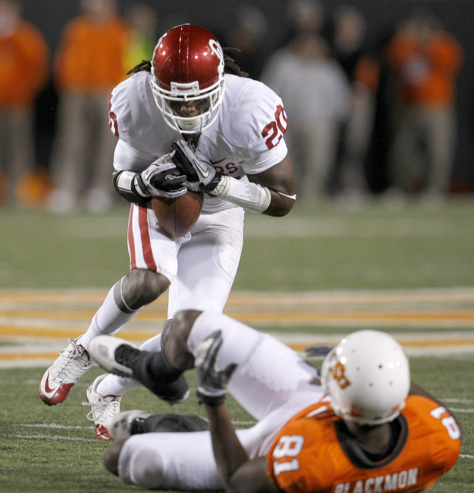 Photo - Oklahoma's Quinton Carter (20) intercepts a pass over Oklahoma State's Justin Blackmon (81) during the Bedlam college football game between the University of Oklahoma Sooners (OU) and the Oklahoma State University Cowboys (OSU) at Boone Pickens Stadium in Stillwater, Okla., Saturday, Nov. 27, 2010. Photo by Bryan Terry, The Oklahoman