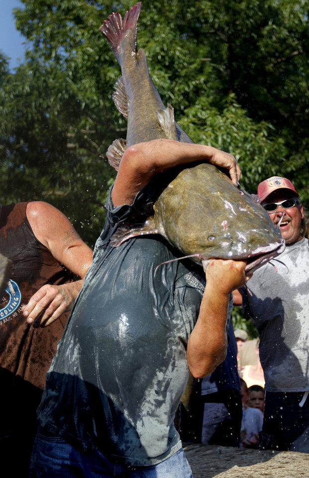 Photo - A noodler carries a big flathead to the weigh-in at the Okie Noodling Tournament in Pauls Valley.  BRYAN TERRY - Photo by Bryan Terry, The Oklaho