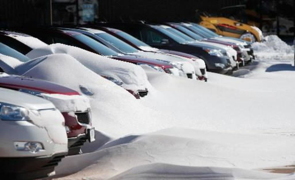 Photo - Drifts of snow covered the fronts of cars Wednesday at Bob Howard Chevrolet near Memorial Road and the Broadway Extension. Central Oklahoma residents Wednesday, Feb, 2, 2011, began digging out from beneath nearly a foot of snow covering the ground after yesterday's winter snowstorm. Photo by Jim Beckel,