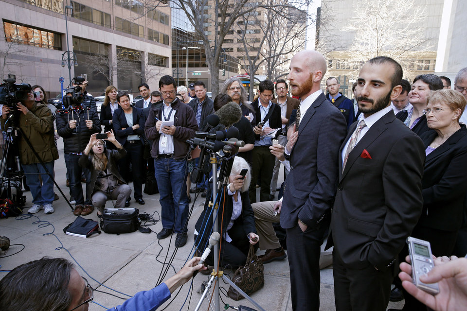 Photo - Plaintiffs challenging Utah's gay marriage ban Moudi Sbeity, right, and his partner Derek Kitchen, take questions from the media after leaving court following a hearing at the U.S. Circuit Court of Appeals in Denver, Thursday, April 10, 2014. The court is to decide if it agrees with a federal judge in Utah who in mid-December overturned a 2004 voter-passed gay marriage ban, saying it violates gay and lesbian couples' rights to due process and equal protection under the 14th Amendment. (AP Photo/Brennan Linsley)