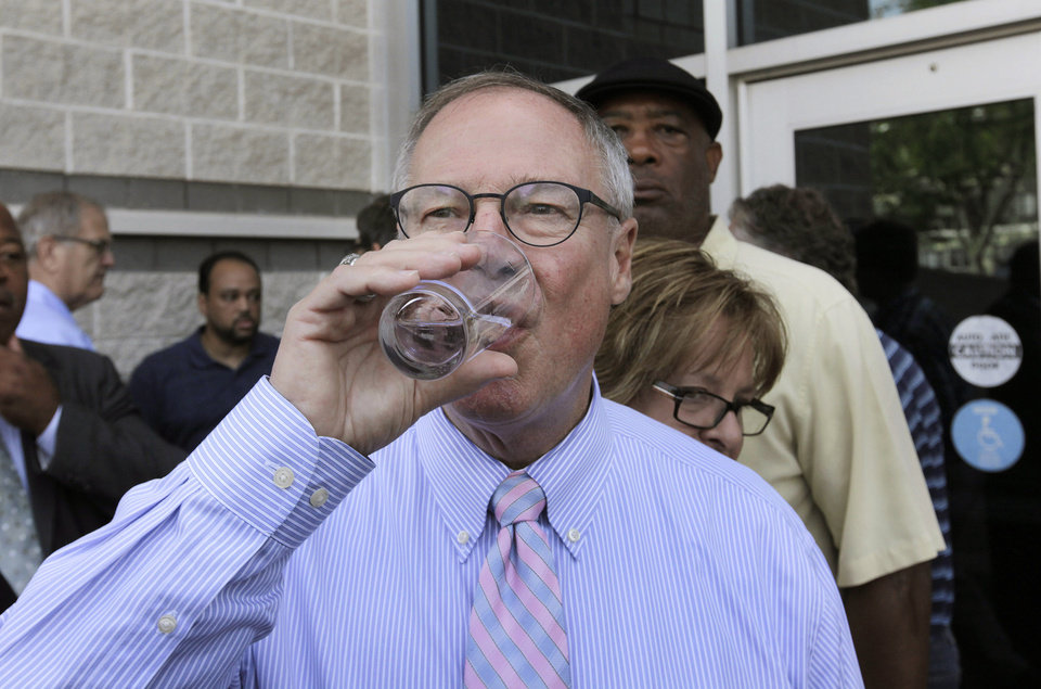 Photo - Toledo Mayor D. Michael Collins drinks a glass of tap water after a news conference in Toledo, Ohio, Monday, Aug. 4, 2014. A water ban that had hundreds of thousands of people in Ohio and Michigan scrambling for drinking water has been lifted, Collins announced Monday. (AP Photo/Paul Sancya)