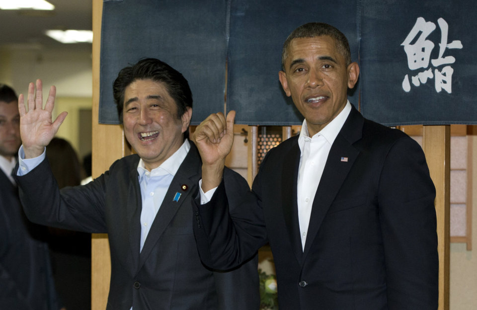Photo - President Barack Obama and Japanese Prime Minister Shinzo Abe depart Sukiyabashi Jiro sushi restaurant in Tokyo, Wednesday, April 23, 2014. Opening a four-country swing through the Asia-Pacific region,  Obama is aiming to promote the U.S. as a committed economic, military and political partner, but the West's dispute with Russia over Ukraine threatens to cast a shadow over the president's sales mission. Japanese at right in the background reads: