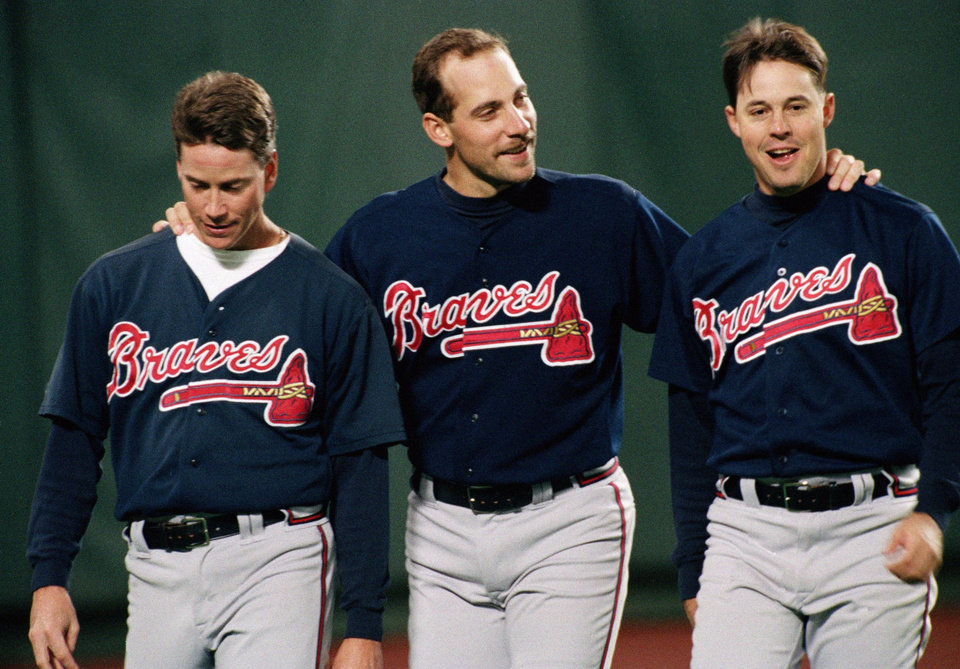 Photo - FILE - In this Oct. 6, 1993 file photo, Atlanta Braves pitchers from left, Tom Glavine, John Smoltz and Greg Maddux share a moment together before a game against the Philadelphia Phillies, in Philadelphia. Maddux and Glavine were elected to baseball's Hall of Fame. The results were announced Wednesday, Jan. 8, 2014. (AP Photo/Doug Mills, File)