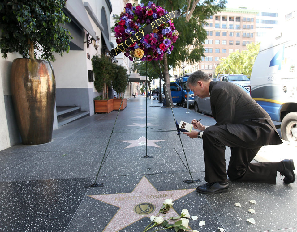 Photo - Hollywood Chamber President Leron Gubler signs a condolence card after flowers are placed on the Hollywood Walk of Fame star of Hollywood legend, Mickey Rooney, on Vine Street on Monday, April 7, 2014, in the Hollywood section of Los Angeles. The iconic actor, Rooney, died at 93 on Sunday, April 6, 2014. Over a four-decade span, he was nominated for four Academy Awards, and received two special Oscars for film achievements, won an Emmy for his TV movie