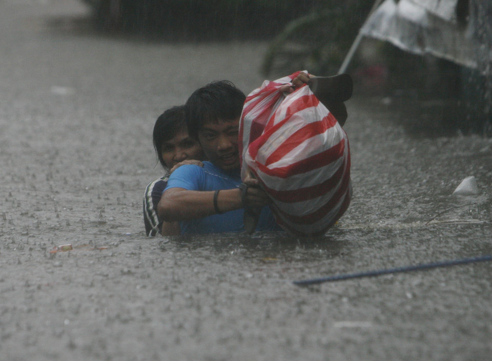 "Residents react during a heavy downpour as they cross a flooded area in San Juan, east of Manila, Philippines, on Wednesday Aug. 8, 2012. Widespread flooding that turned half of the Philippine capital into a ""water world"" eased long enough for rescuers on rubber boats to reach many of the distressed residents still marooned in submerged villages Wednesday. (AP Photo/John Javellana) ORG XMIT: XAF134"
