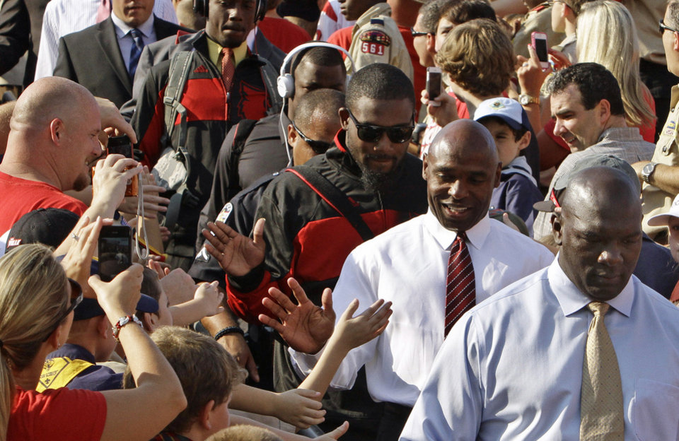 Photo - Louisville football coach Charlie Strong, second from right,  behind strength coach Pat Moorer, greets fans, including several hundred Cub Scouts and Boy Scouts as the team enters Cardinal Stadium before the start of their NCAA college football game against Eastern Kentucky in Louisville, Ky., Saturday, Sept. 7, 2013. (AP Photo/Garry Jones)