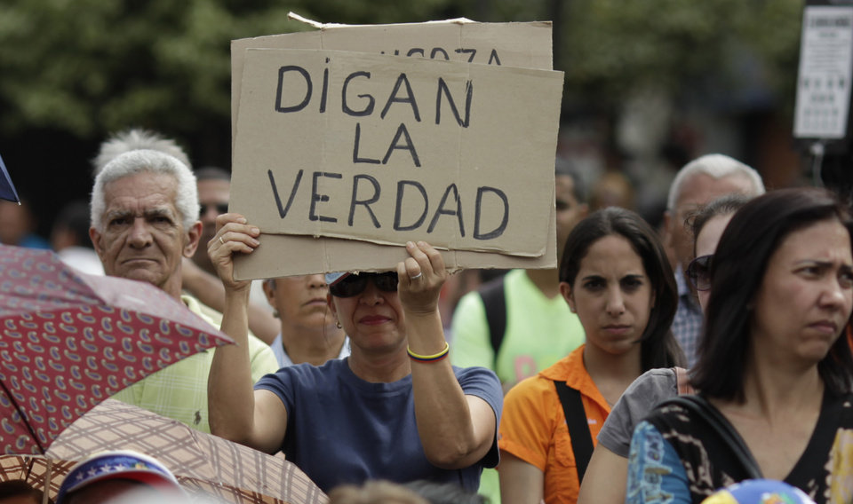 Photo - An opponent of Venezuela's President Hugo Chavez holds up a sign that reads in Spanish,