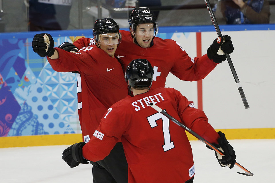 Photo - Switzerland forward Nino Niederreiter, left, Switzerland forward Simon Moser, right, and Switzerland defenseman Mark Streit (7) celebrate Switzerland's 1-0 victory over Latvia during the 2014 Winter Olympics men's ice hockey game at Shayba Arena, Wednesday, Feb. 12, 2014, in Sochi, Russia. (AP Photo/Petr David Josek)