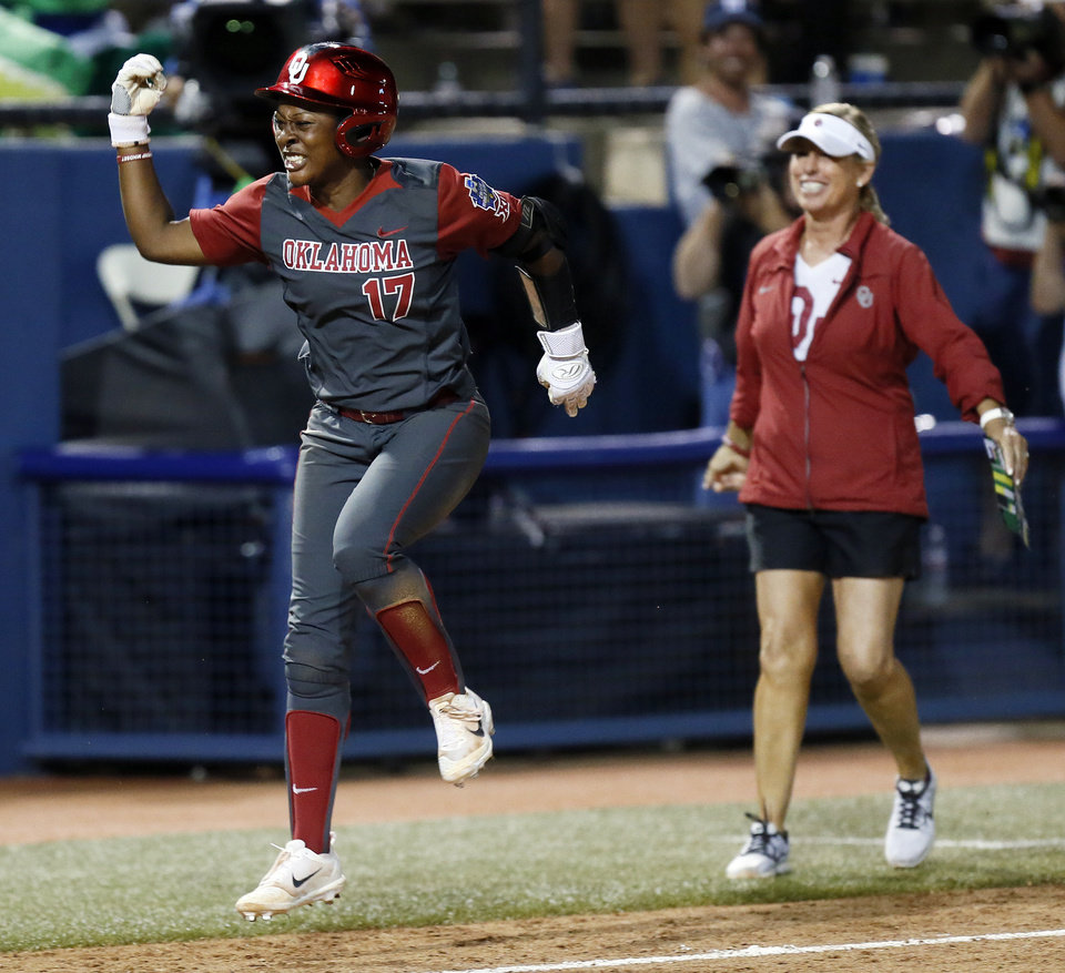 Photo - OU's Shay Knighten (17) reacts in front of coach Patty Gasso as she runs home after hitting a three-run home run to give the Sooners the lead for good in the top of the 17th inning during Game 1 in the championship series of the Women's College World Series between the Oklahoma Sooners (OU) and Florida Gators at ASA Hall of Fame Stadium in Oklahoma City, Monday, June 5, 2017. OU won 7-5 in 17 innings. Photo by Nate Billings, The Oklahoman