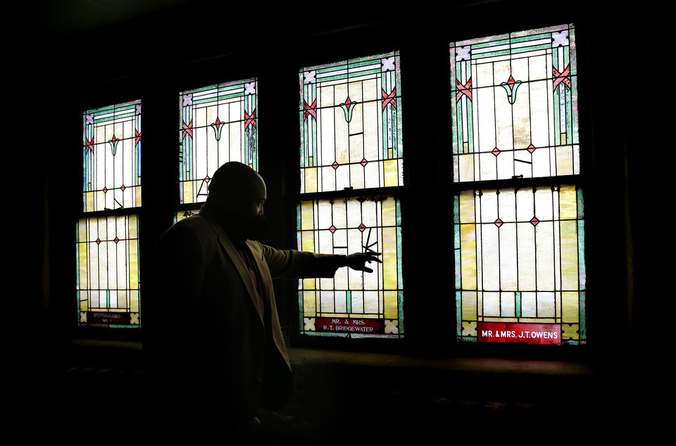 Photo - The Rev. Robert Turner talks about the stained-glass windows at the Vernon A.M.E Church in the Greenwood district in Tulsa, Okla., Wednesday, July 22, 2020. Photo by Sarah Phipps, The Oklahoman