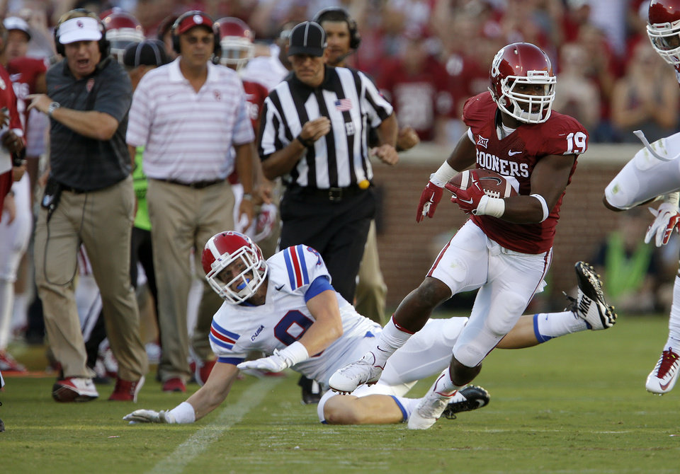 Photo - Oklahoma's Eric Striker (19) returns the ball after a blocked field goal attempt as during a college football game between the University of Oklahoma Sooners (OU) and the Louisiana Tech Bulldogs at Gaylord Family-Oklahoma Memorial Stadium in Norman, Okla., on Saturday, Aug. 30, 2014. Photo by Bryan Terry, The Oklahoman
