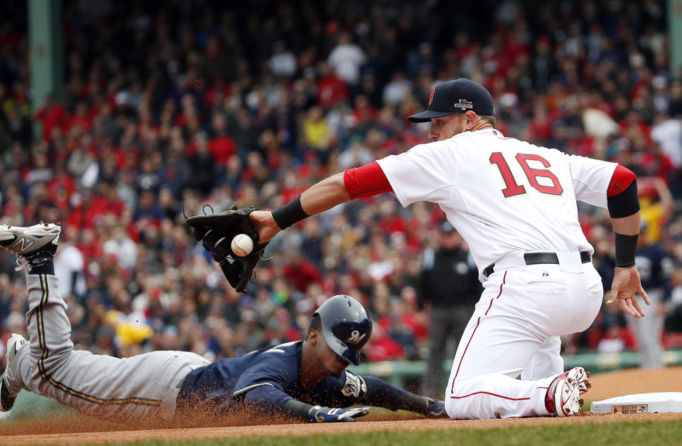 Photo - Milwaukee Brewers' Jean Segura slides in safely with a triple as Boston Red Sox third baseman Will Middlebrooks (16) takes in the throw from left field during the first inning of a baseball game at Fenway Park in Boston, Friday, April 4, 2014. (AP Photo/Elise Amendola)