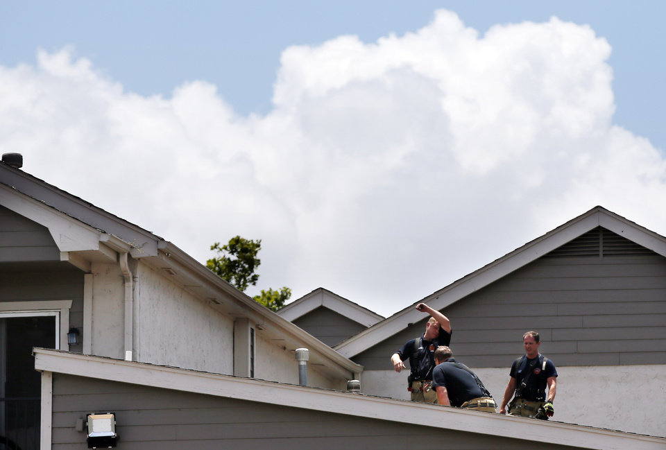 Photo - Oklahoma City firefighters work on the roof after putting out an apartment fire in the 7000 block of W Britton Rd. in Oklahoma City, Monday, July 1, 2019. [Nate Billings/The Oklahoman]