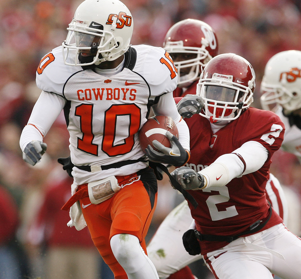 Photo - Oklahoma State's Tommy Devereaux (10) gets past Oklahoma's Brian Jackson (2) during the first half of the college football game between the University of Oklahoma Sooners (OU) and the Oklahoma State University Cowboys (OSU) at the Gaylord Family-Memorial Stadium on Saturday, Nov. 24, 2007, in Norman, Okla. 