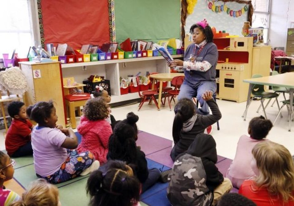 Photo -  Glorene Stewart reads to kindergarten students at North Highland Elementary School in Oklahoma City. Stewart, a longtime teaching assistant, is participating in a program that pays for paraprofessionals of color to become certified teachers. [JIM BECKEL/THE OKLAHOMAN]