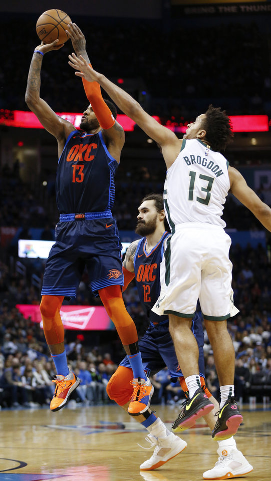 Photo - Oklahoma City's Paul George (13) shoots in front of Steven Adams (12) as Milwaukee's Malcolm Brogdon (13) defends in the third quarter during an NBA basketball game between the Milwaukee Bucks and the Oklahoma City Thunder at Chesapeake Energy Arena in Oklahoma City, Sunday, Jan. 27, 2019. Oklahoma City won 118-112. Photo by Nate Billings, The Oklahoman