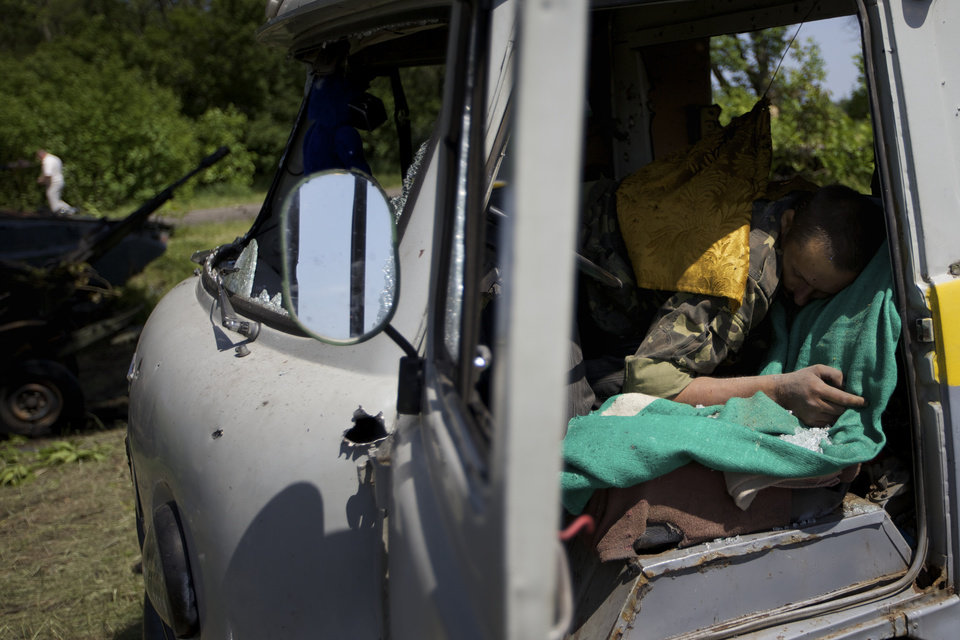 Photo - A body seen in a destroyed car near the village of Blahodatne, eastern Ukraine, on Thursday, May 22, 2014. At least 11 Ukrainian troops were killed and about 30 others were wounded when Pro-Russians attacked a military checkpoint, the deadliest raid in the weeks of fighting in eastern Ukraine. Three charred Ukrainian armored infantry vehicles, their turrets blown away by powerful explosions, and several burned vehicles stood at the site of the combat. (AP Photo/Ivan Sekretarev)