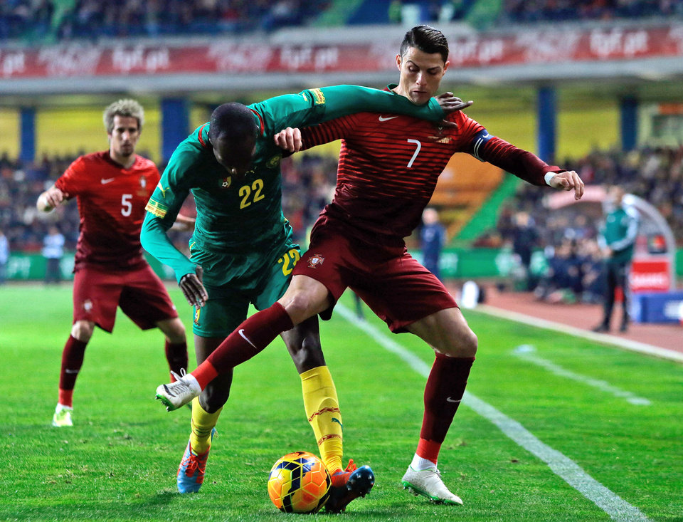 Photo - Portugal's Cristiano Ronaldo, right, fights for the ball with Cameroon's Allan Nyom during their friendly soccer match Wednesday, March 5 2014, in Leiria, Portugal. The game is part of both teams' preparation for the World Cup in Brazil. (AP Photo/Armando Franca)