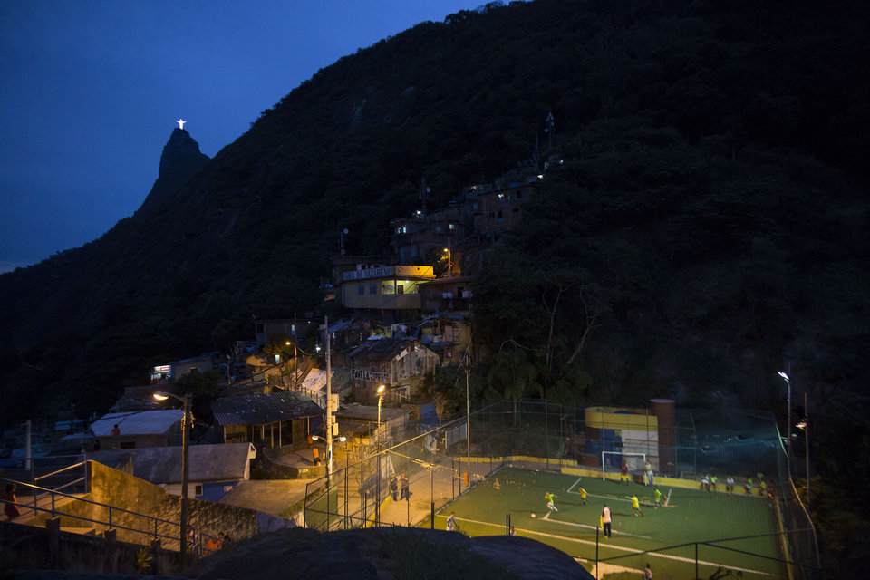 "Photo - In this June 6, 2014 photo, people play soccer at the Dona Marta slum, backdropped by the Christ the Redeemer statue and Corcovado Mountain in Rio de Janeiro, Brazil. City - or charity - run ""escolinhas,"" or soccer schools, operate in nearly all of the slums, from the Dona Marta shantytown, which is ensconced in the middle-class Botafogo neighborhood, to Mangueira, a historic slum overlooking the mythical Maracana Stadium, where six World Cup matches plus the final are to be held. (AP Photo/Felipe Dana)"